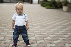 Enfant en bas âge sérieux mignon posant dans des blues-jean et T-shirt blanc et penser à l'avenir Copiez l'espace Photo libre de droits