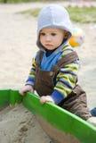 Enfant en bas âge s'asseyant près du bac à sable Photos libres de droits