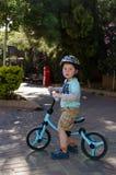 Enfant en bas âge s'asseyant sur sa bicyclette d'équilibre Photo libre de droits
