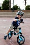 Enfant en bas âge s'asseyant sur sa bicyclette d'équilibre Photo stock