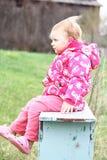 Enfant en bas âge s'asseyant sur un banc. Photographie stock