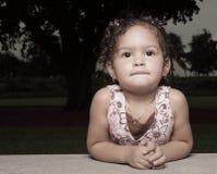Enfant en bas âge se penchant sur ses coudes Photo stock