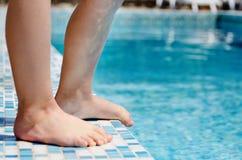 Enfant en bas âge se tenant au bord d'une piscine Photographie stock
