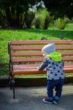 Enfant en bas âge se tenant près du banc Photographie stock