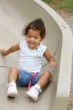 Enfant en bas âge sur la glissière de cour de jeu Photo stock