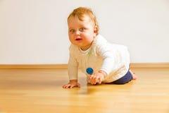 Enfant en bas âge sur un plancher de parquet images stock