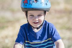 Enfant en bas âge sur un vélo de Strider à un casque de port de cendrée Photo stock