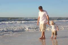 Enfant en bas âge tenant la main du père tout en marchant dans l'océan sur la plage Photo libre de droits