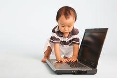 Enfant en bas âge curieux avec l'ordinateur portatif Photo stock