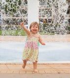 Enfant en bas âge jouant avec de l'eau Images stock