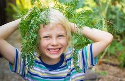 Enfant en bonne santé heureux avec le dessus de carotte dans le potager photos libres de droits