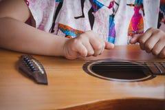Enfant en gros plan jouant la guitare Concept de liftstyle, de l'étude, de passe-temps, de musicien, de rêve et d'imagination Images stock