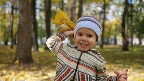 Enfant en parc d'automne ayant l'amusement jouant avec les feuilles, promenades à l'air frais banque de vidéos