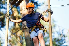 Enfant en parc d'aventure de forêt Enfant dans le casque orange et montées bleues de T-shirt sur la haute traînée de corde Qualif image stock