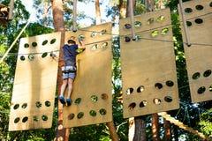 Enfant en parc d'aventure de forêt Enfant dans le casque orange et montées bleues de T-shirt sur la haute traînée de corde Qualif photographie stock libre de droits