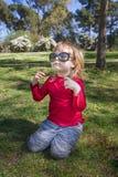 Enfant en parc jouant avec de grandes lunettes de soleil Photographie stock libre de droits