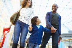 Enfant en voyage au centre commercial avec des parents photos stock