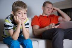 Enfant ennuyé s'asseyant sur le sofa Photo stock
