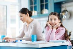 Enfant ennuyé se tenant près de son fonctionnement de maman image stock