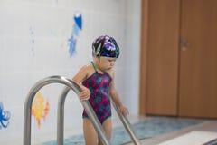 Enfant entrant dans la piscine photos stock