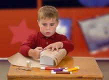 Enfant enveloppant un cadeau photo stock