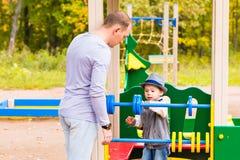 Enfant espiègle avec le père au terrain de jeu extérieur Image stock