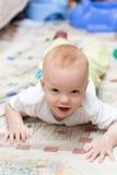 Enfant espiègle rampant sur le tapis Image stock