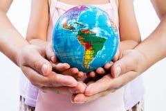 Enfant et adulte tenant un globe du monde dans des mains Photos stock