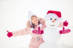 Enfant et bonhomme de neige en hiver Photo libre de droits