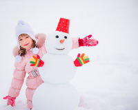 Enfant et bonhomme de neige en hiver Images stock