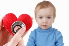 Enfant et cardiologue, symbole de coeur à disposition, stéthoscope Photographie stock
