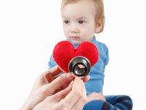 Enfant et cardiologue, symbole de coeur à disposition, stéthoscope Photos stock