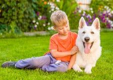 Enfant et chien de berger suisse blanc ensemble sur l'herbe verte Images libres de droits