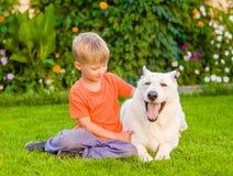 Enfant et chien de berger suisse blanc ensemble sur l'herbe verte Photos stock