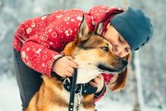 Enfant et chien de fille étreignant et jouant extérieur Photo libre de droits