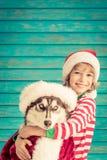 Enfant et chien heureux le réveillon de Noël Photos stock