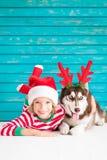Enfant et chien heureux le réveillon de Noël Image stock