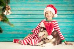 Enfant et chien heureux le réveillon de Noël Photographie stock libre de droits
