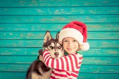 Enfant et chien heureux le réveillon de Noël Photographie stock