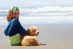 Enfant et chiot à la plage Image libre de droits