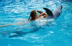 enfant et dauphins dans l'eau bleue Le dauphin a aidé la thérapie Photographie stock libre de droits