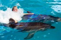 Enfant et dauphins heureux dans l'eau bleue Photo libre de droits