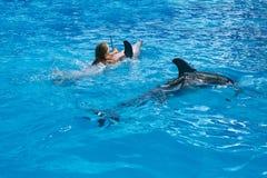 Enfant et dauphins heureux dans l'eau bleue Images stock