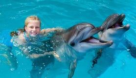 Enfant et dauphins heureux dans l'eau bleue Photos stock