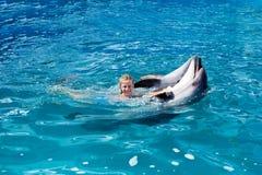 Enfant et dauphins heureux dans l'eau bleue Image libre de droits