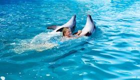 Enfant et dauphins heureux dans l'eau bleue Photo stock