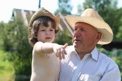 Enfant et grand-père dans des chapeaux de cowboy Photographie stock libre de droits
