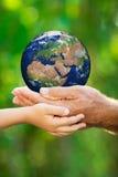Enfant et homme tenant la terre dans des mains Photo stock