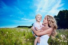 Enfant et jeune femme avec des fleurs jouant dans le domaine photographie stock