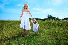 Enfant et jeune femme avec des fleurs jouant dans le domaine la fleur de jour donne à des mères le fils de momie à Photographie stock